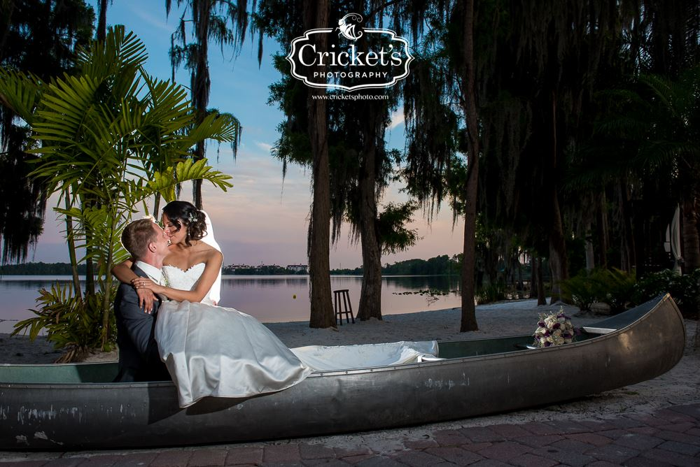 Paradise Cove - bride and groom kissing in canoe on sandy lakeshore