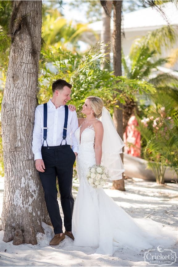 Paradise Cove - bride and groom standing in sand under palm tree