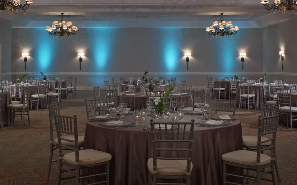 Renaissance-Orlando-Hotel-Airport-Basic silver/grey table setting and chairs with turquoise, light blue up lighting on the walls