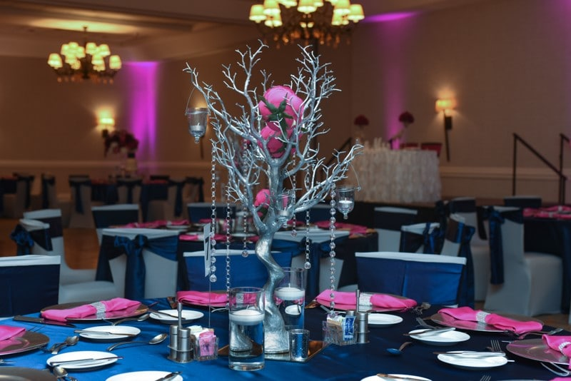 Renaissance-Orlando-Hotel-Airport-Silver branch centerpiece with crystals hanging down surrounded by navy blue and pink table settings at indoor reception.
