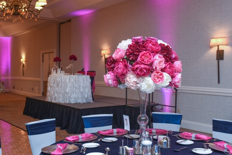 Renaissance-Orlando-Hotel-Airport-Tall clear pink floral centerpiece on a navy blue and pink table setting inside reception with pink drop lights in background