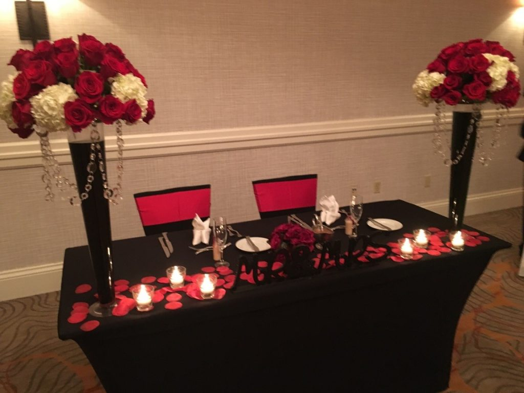Renaissance-Orlando-Hotel-Airport-Bride and Groom table at reception with Red and white rose tall centerpieces and white candles