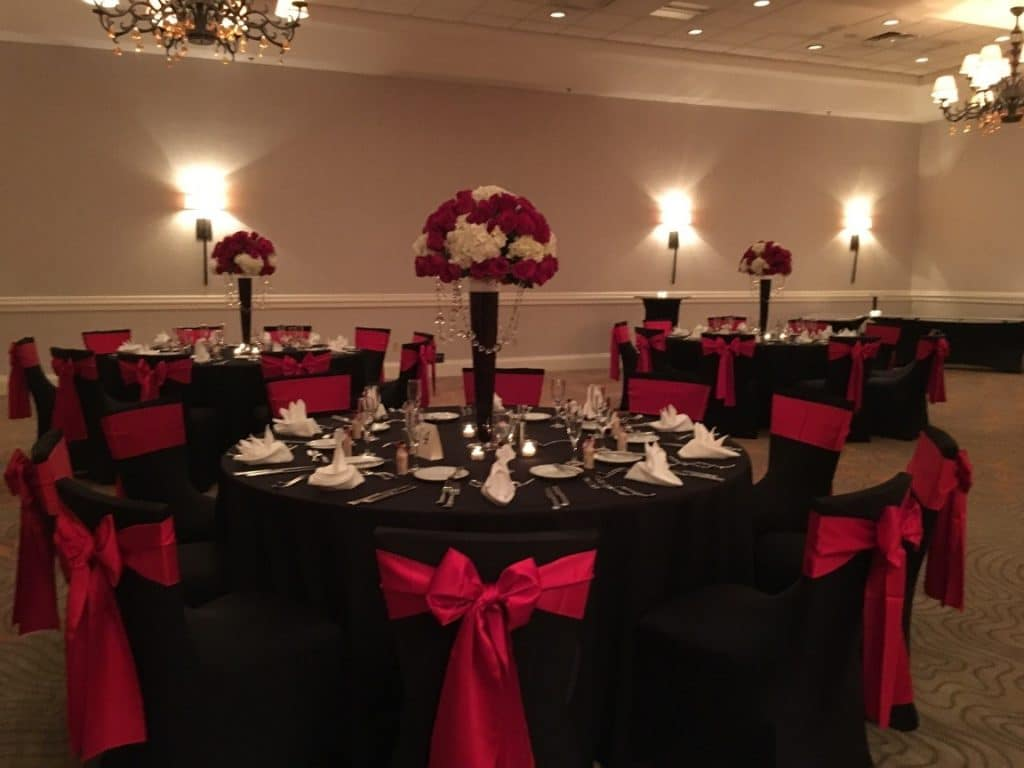 Renaissance-Orlando-Hotel-Airport-Rectangular table with tall white and red rose center piece, black table setting and red accent ribbon on chairs