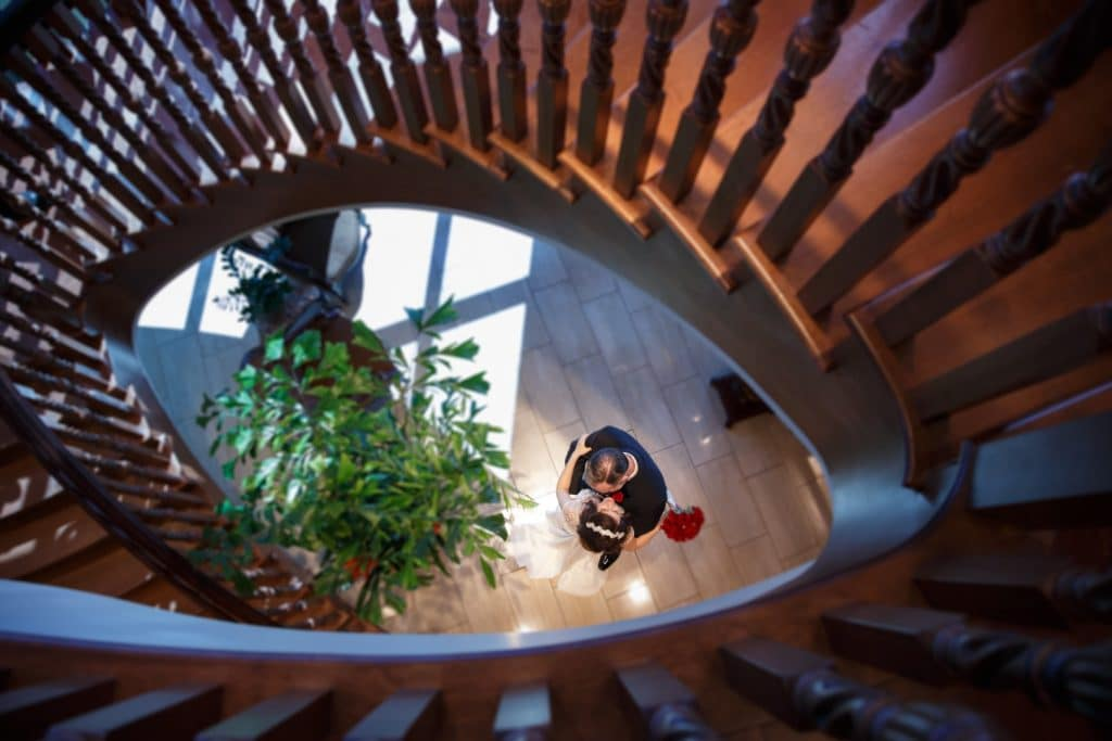 Tavares-Pavilion-on-the-Lake-Looking down at Bride and Groom kissing at the bottom of the stair case