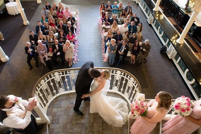 The-Ballroom-on-Church-Street-Bride and Groom kissing on staircase in front of guests indoors