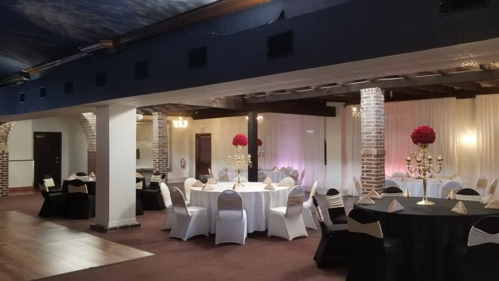 The Bella Room - black and white reception tables among brick columns