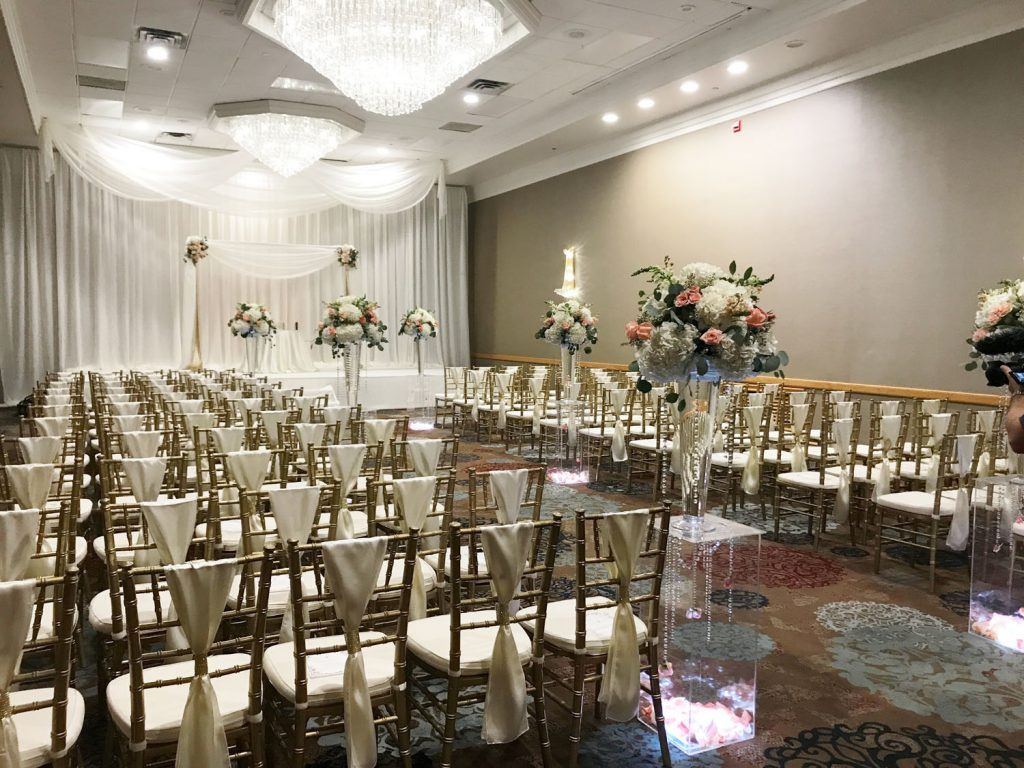 The Florida Hotel and Conference Center - long ceremony room with gold chiavari chairs, chandeliers, and fabric drapery over altar