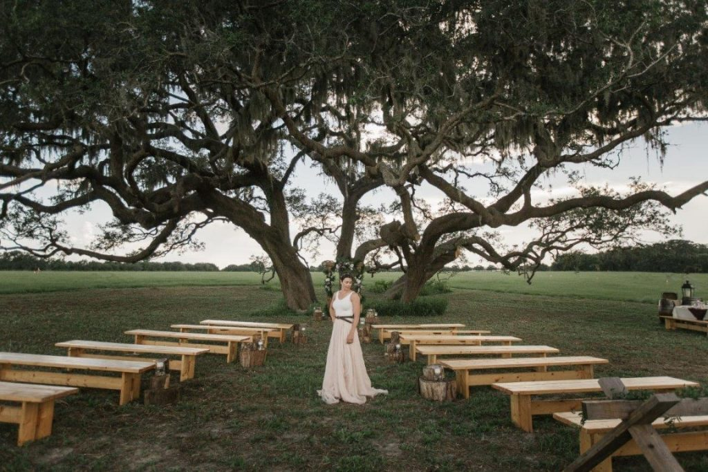 The-Villages-Polo-Club-Bride standing in outdoor aisle in front of large oak trees