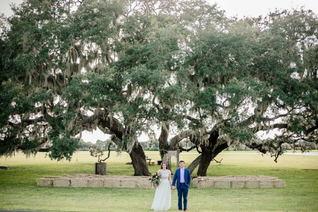 The-Villages-Polo-Club-Couple holding hands in front of large oak trees