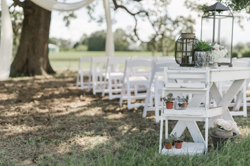 Villages Polo Club - white folding chairs turn a rolling field into an elegant wedding ceremony