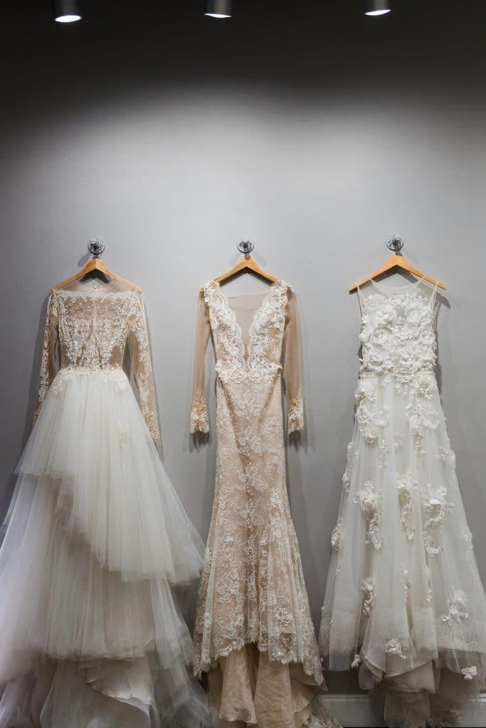 three wedding dresses hanging on white wall