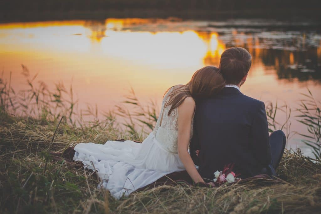 bride and groom by lake at sunset