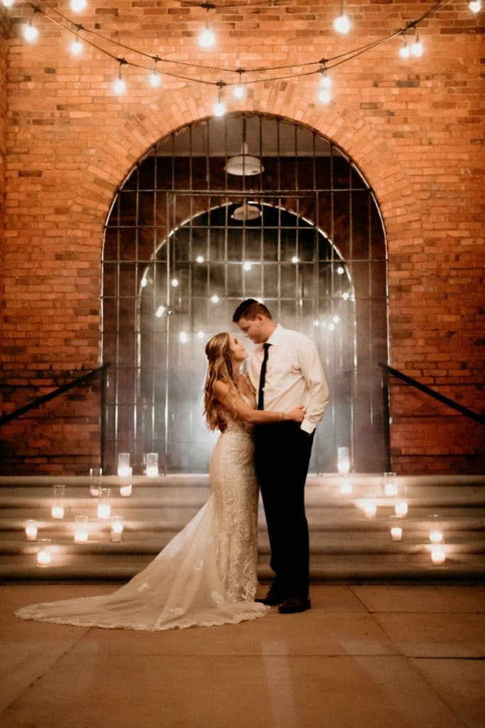 Venue-1902-Happy couple standing on steps outside front venue gates with candles and lights