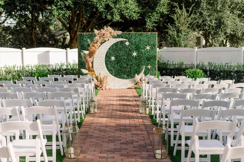Venue-1902-Floral moon and greenery backdrop by end of ceremony aisle.
