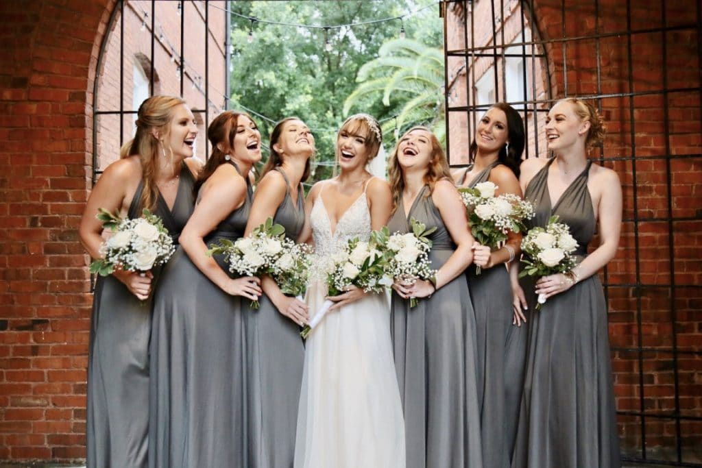 Venue-1902-Bride and bridesmaids laughing while holding flowers