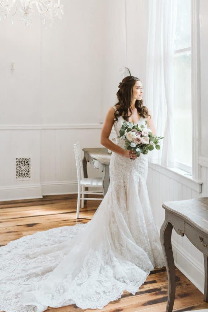Venue-1902-Bride gazing out window with bouquet