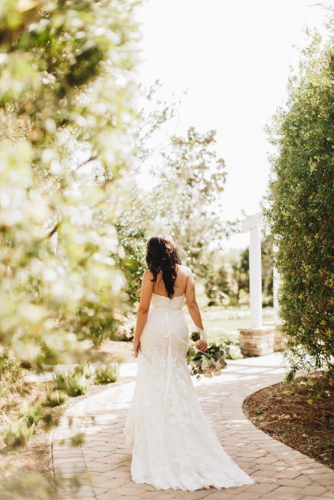 beautiful bride walking down tree-lined path