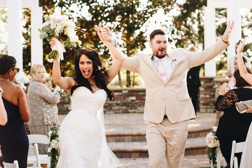 bride and groom celebrating during recessional