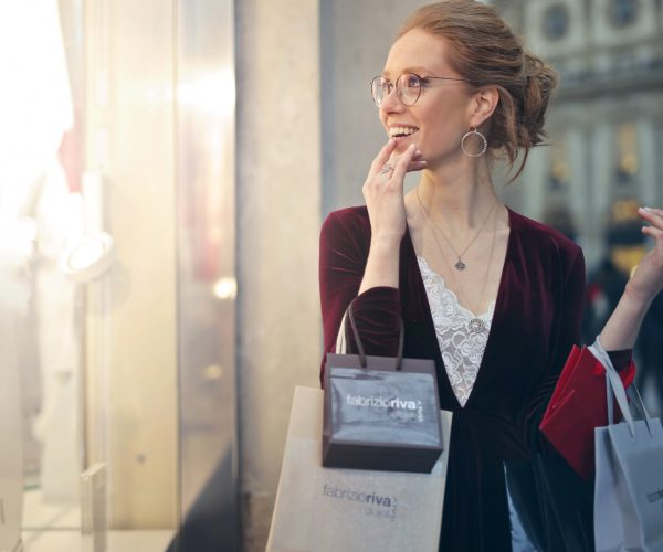 woman looking in shop window with shopping bags