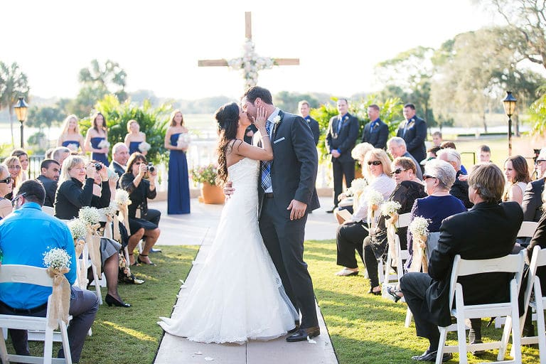 Anna Christine Events - bride and groom kissing halfway down aisle at ceremony