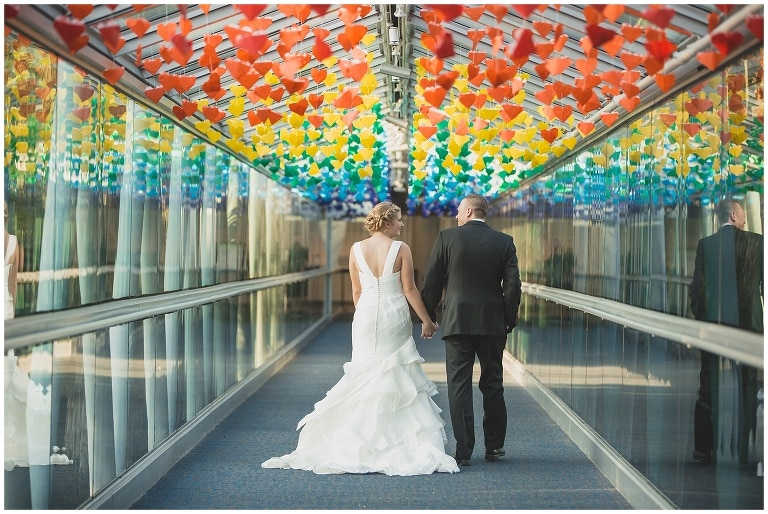 Anna Christine Events - bride and groom walking down glass hallway with rainbow origami hearts hanging from ceiling