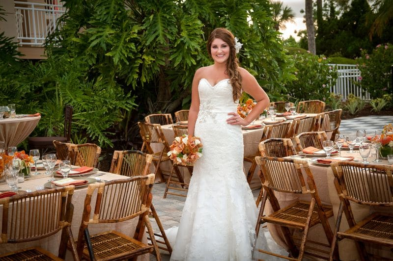 Anna Christine Events - bride posing next to rustic tropical reception tables