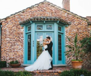 Rudy & Marta Photography - bride and groom kissing in front of bright blue door