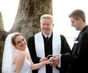 A Beautiful Ceremony - bride laughing while groom puts ring on her