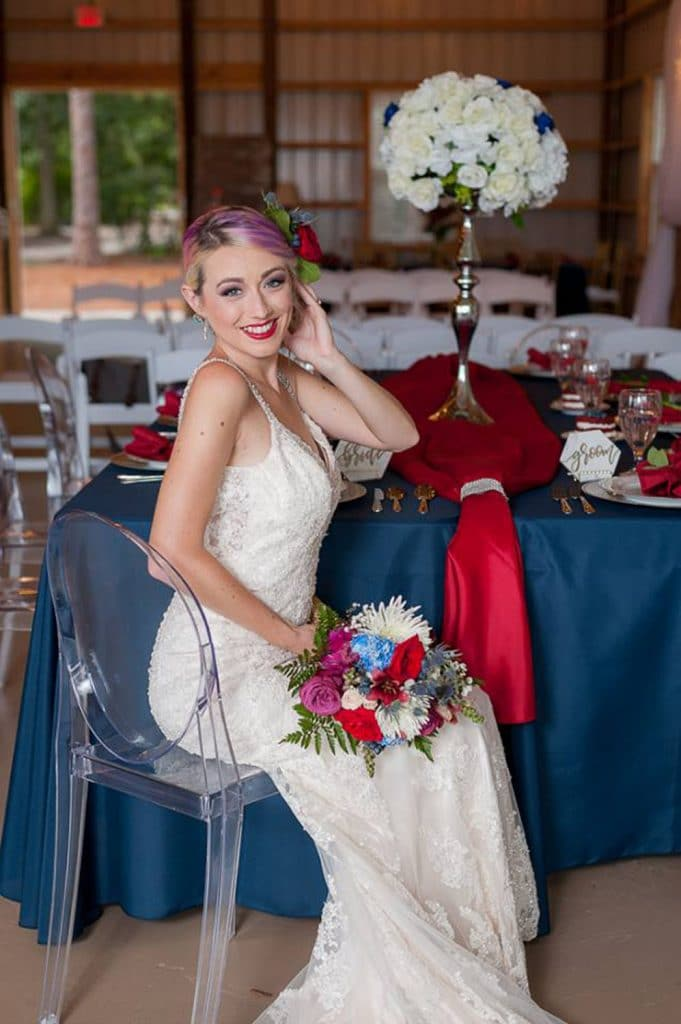 Blue View Event Barn - bride poses at reception table in clear chair
