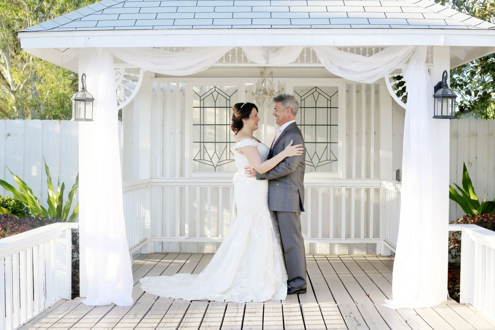 Celebration Gardens- bride and groom under white porch