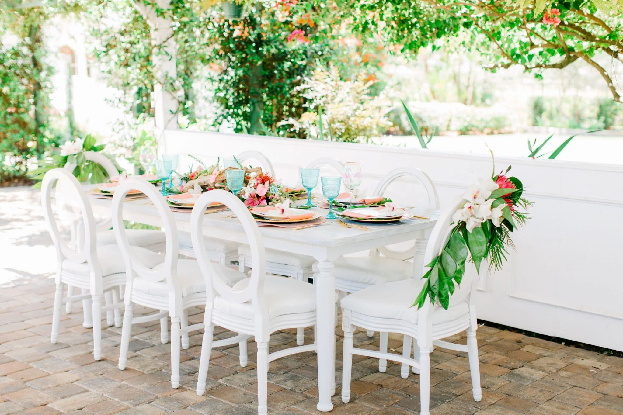 outside table set up all in white with greens and blue glasses