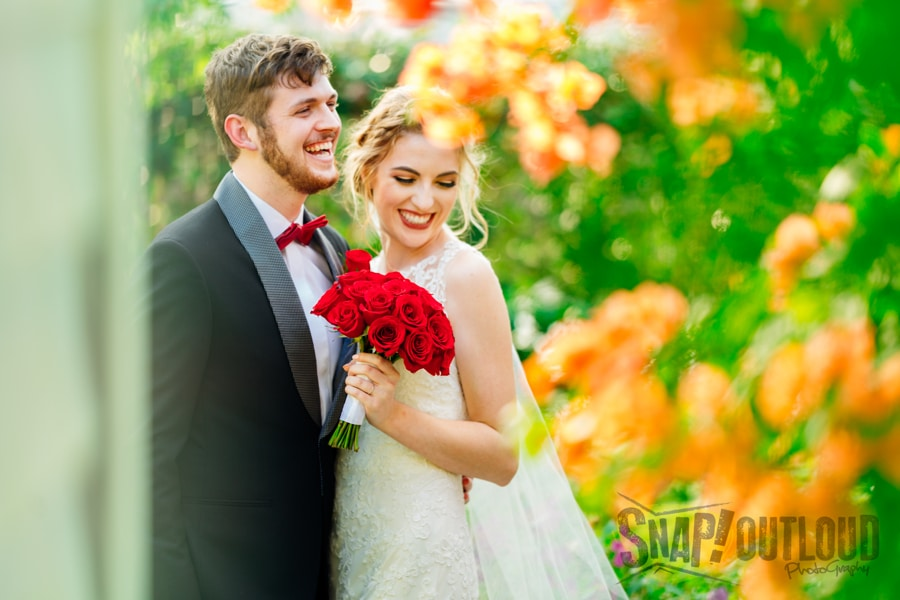 bride and groom smiling outside with red rose bouquet