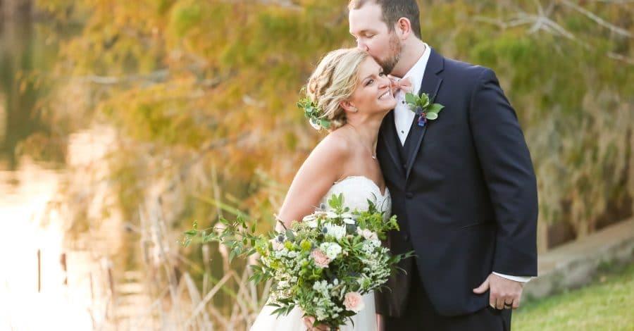Live Happy Studio - groom kissing bride beside lake