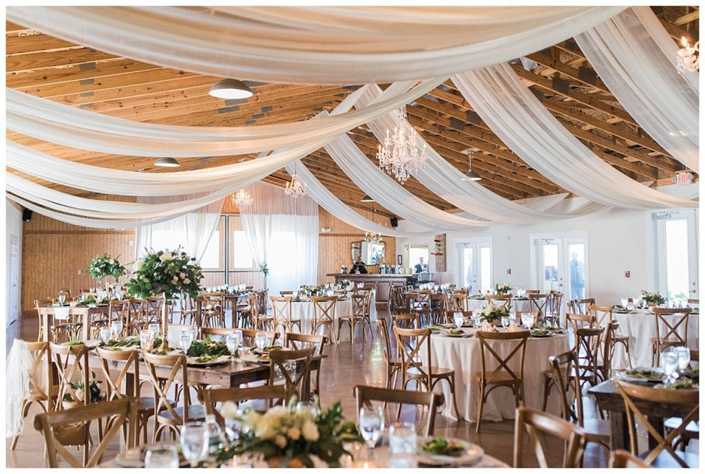 Up the Creek Farms - rustic reception hall with white drapery accents and chandeliers