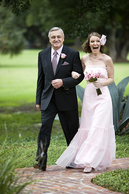 bride with big smile while father walks her up aisle