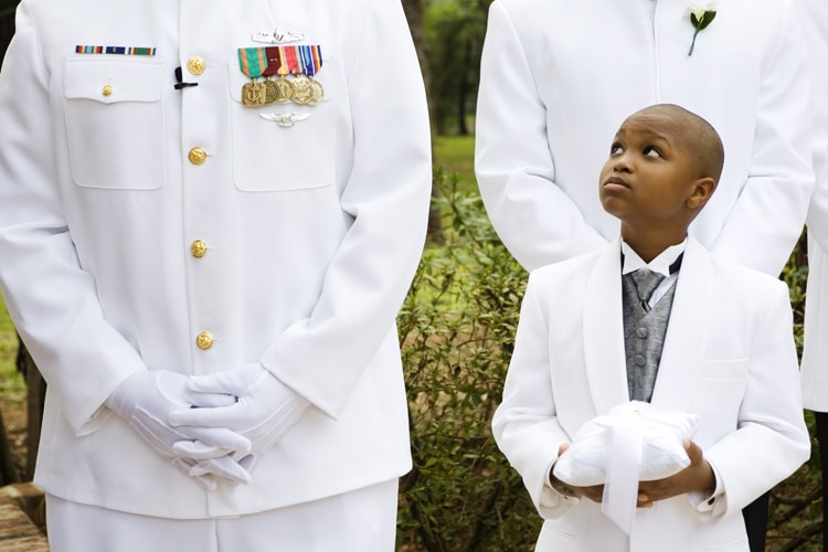 young ringbearer looks up at man in military uniform