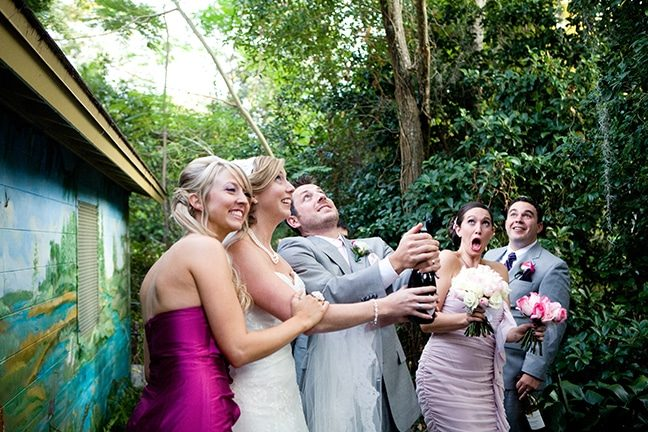 groom pops cork while bride and guests laugh