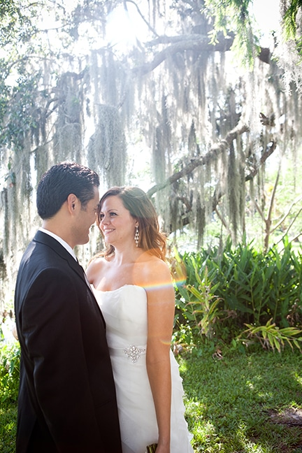 bride and groom gazing into each other's eyes beneath moss covered oak tree