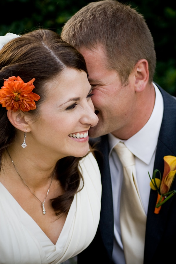 bride laughing while groom whispers in her ear