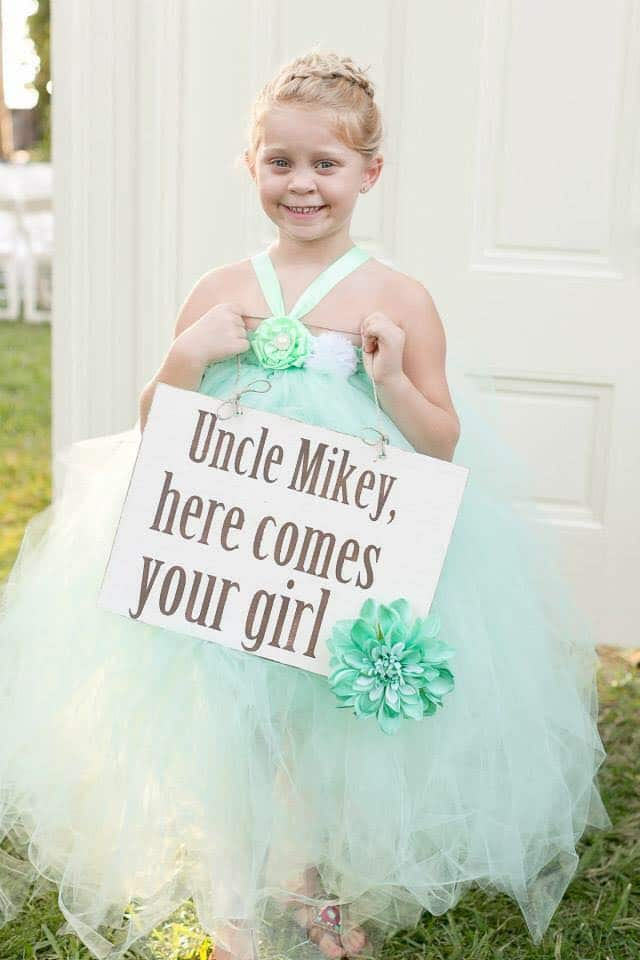 "flower girl holding sign ""Uncle Mikey, here comes your girl"""