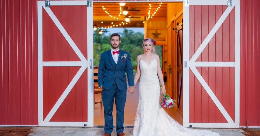 Blue View Event Barn - newlyweds holding hands in doorway of barn
