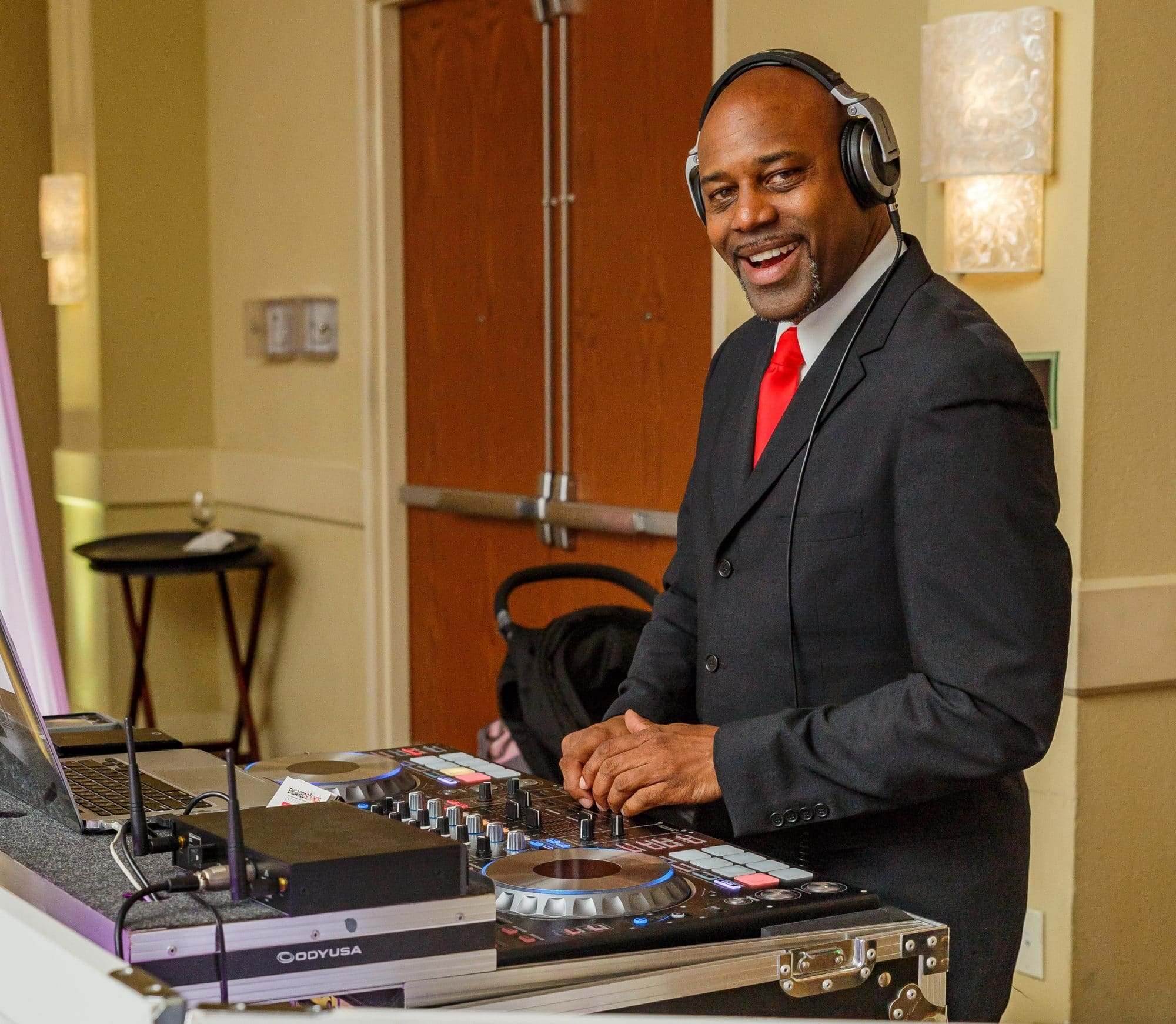 well-dressed DJ behind sound equipment