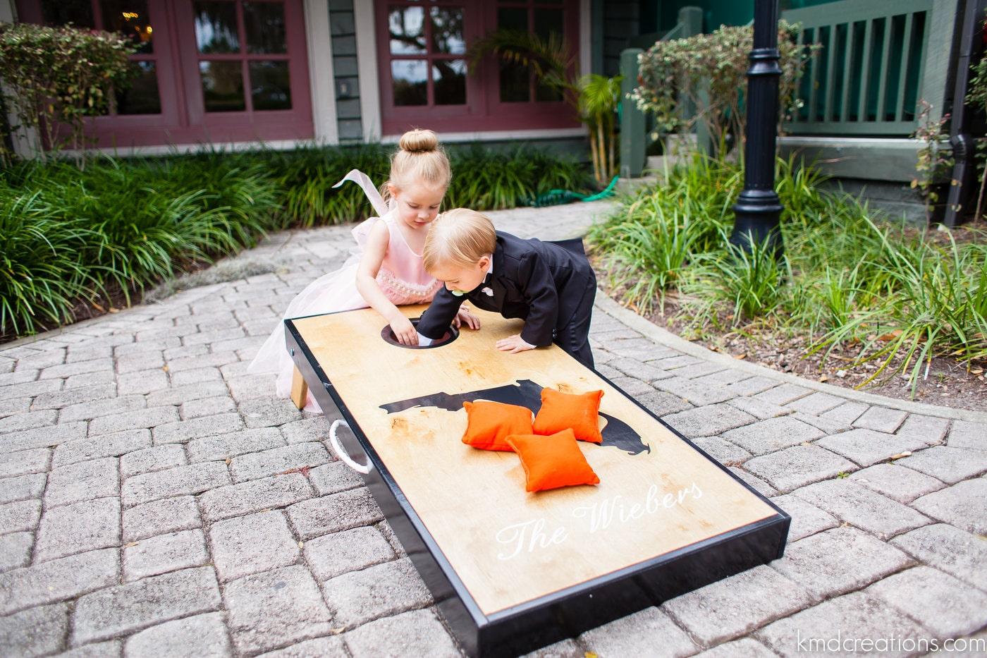 toddlers playing with cornhole