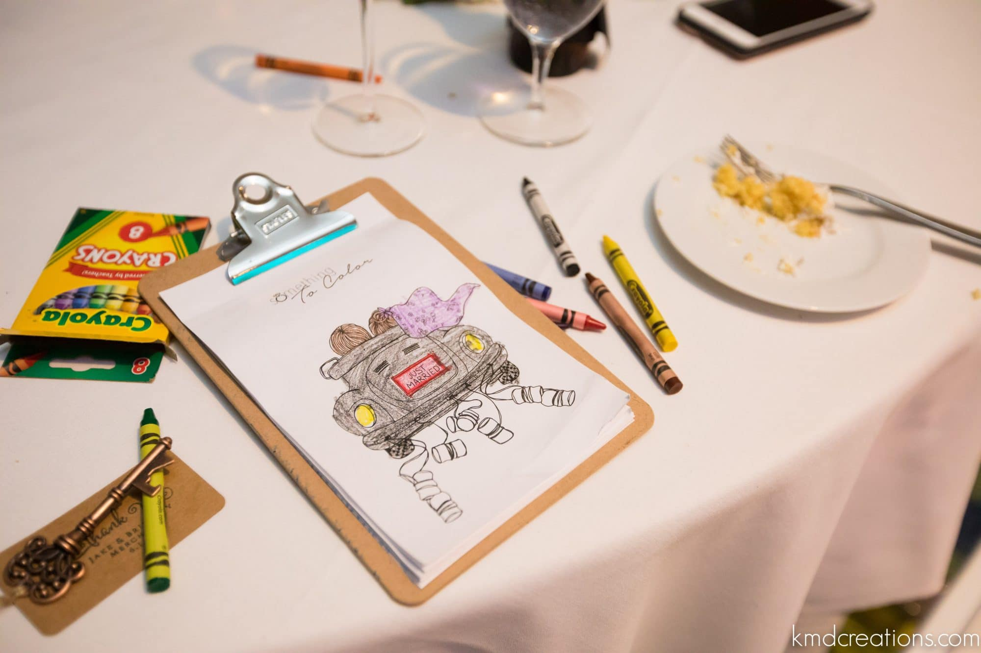 crayons and coloring pages at reception table