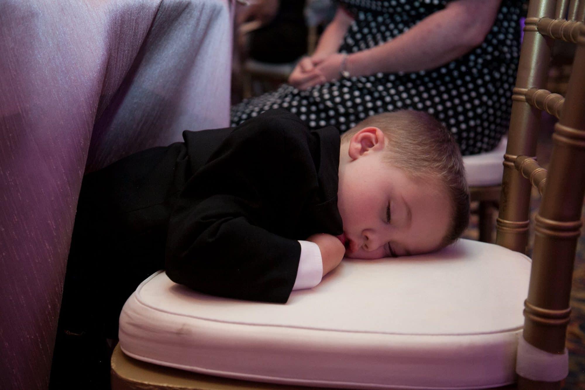 toddler boy asleep on chair