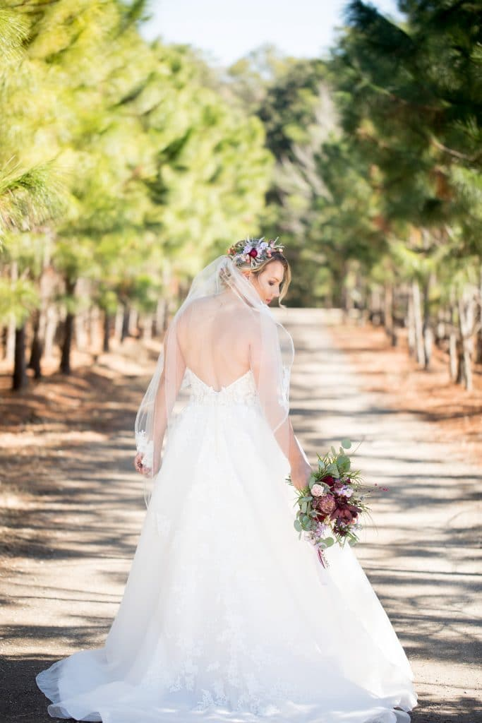 Bride holding loose, romantic bouquet in shades of dark wine