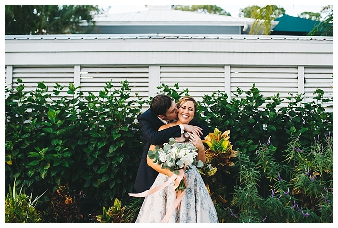 groom kissing bride on cheek while she holds white and sage bouquet
