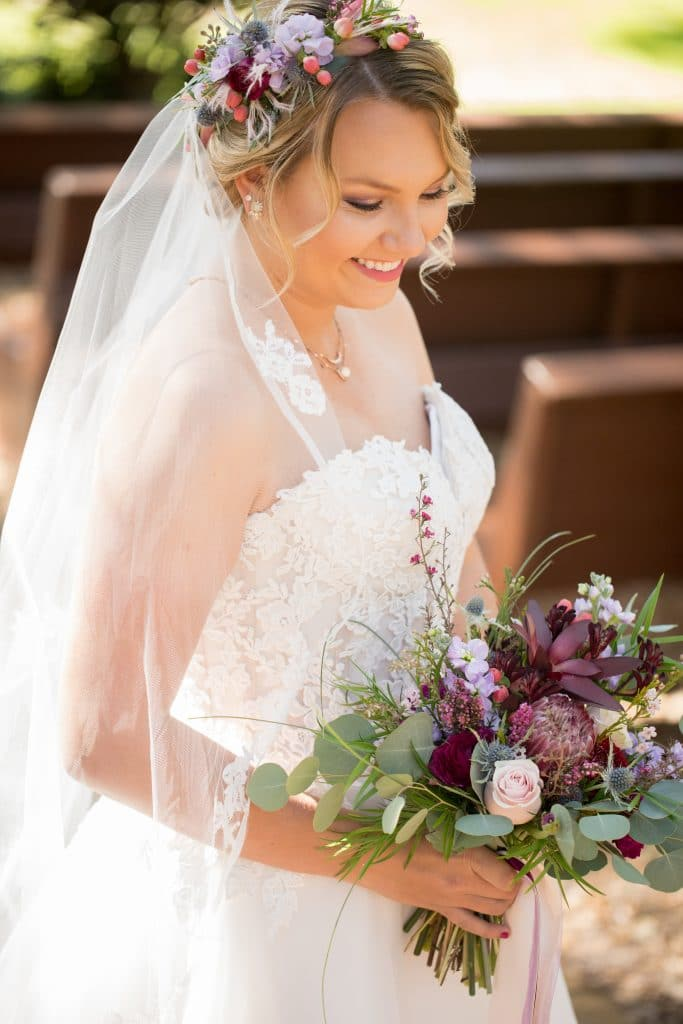 Smiling bride with dynamic bouquet and floral hair accents