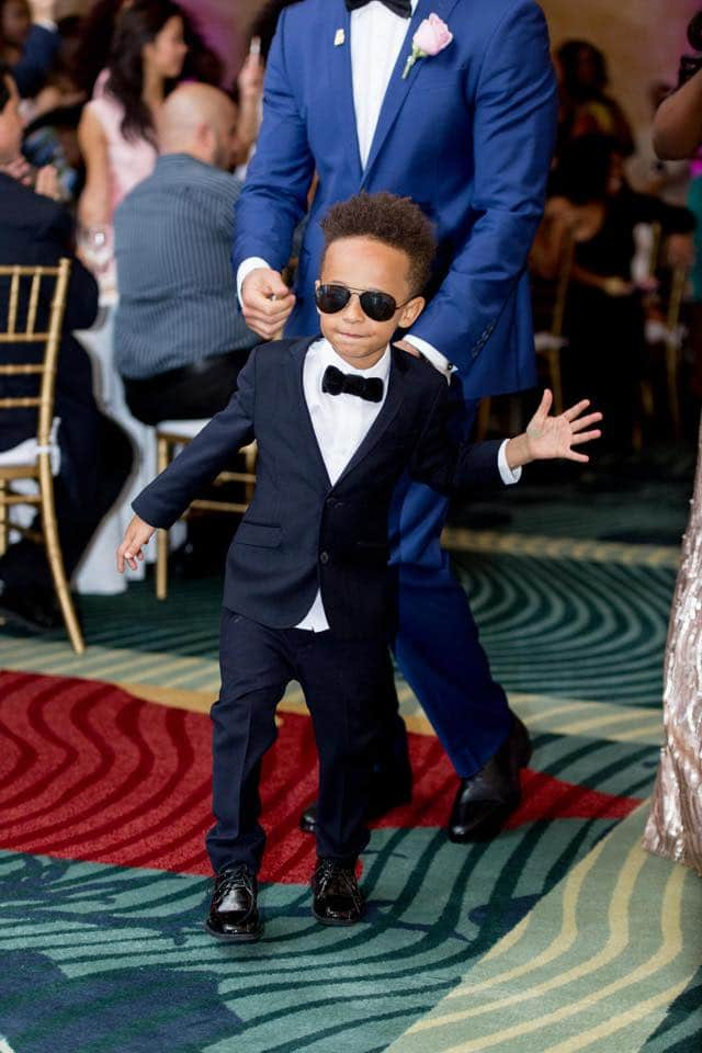 handsome ring bearer in suit and sunglasses