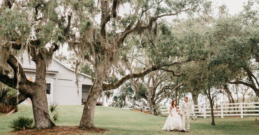 Up the Creek Farms - bride and groom walking among mossy oaks